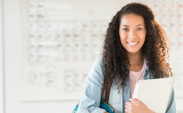 Portrait of beautiful teenage student with shoulder bag and books standing in chemistry class_47773