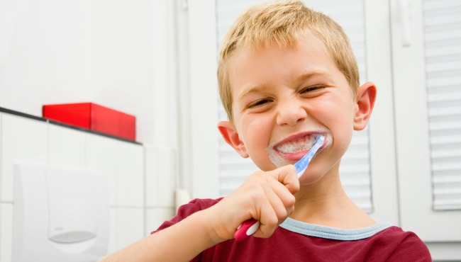 Boy brushing teeth in bathroom_47197