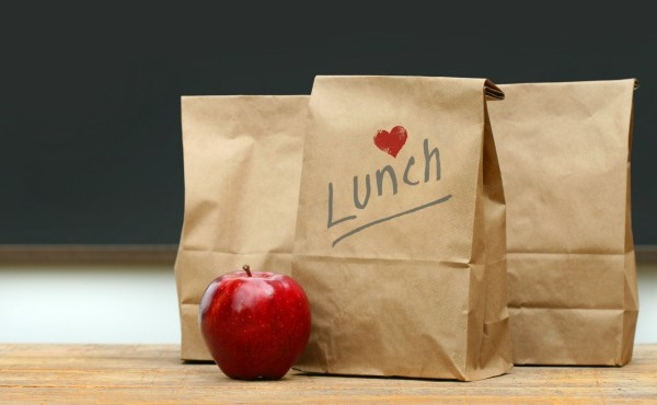 Paper lunch bags with red apple on school desk_48869