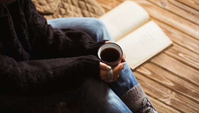 Woman with beautiful manicure holding a gray cup of tea and reading a book_52025