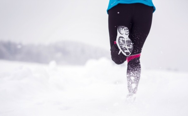 Athlete woman is running during winter training outside in cold snow weather._53812