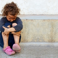 poor, sad little child girl sitting against the concrete wall_64331