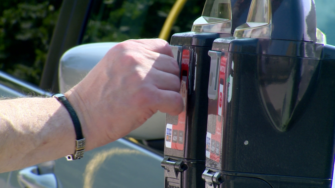 Man puts money in parking meter