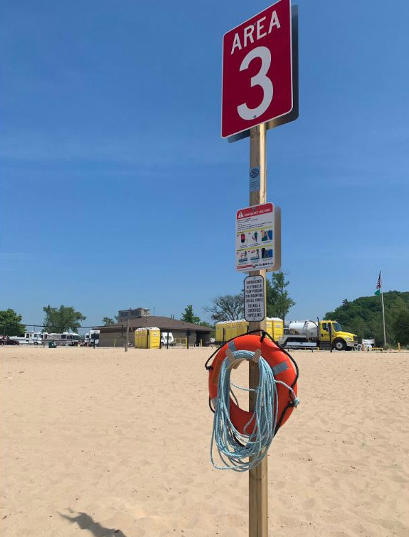 Life ring and zone 3 sign on Lake Michigan beach in Grand Haven