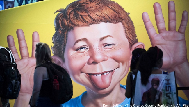 """FILE - In this July 20, 2017 file photo the face of Alfred E. Neuman is framed by attendees at the DC booth during the first day of Comic-Con International at the San Diego Convention Center in San Diego, Calif. MAD, the long-running satirical magazine that influenced everyone from """"Weird Al"""" Yankovic to the writers of """"The Simpsons,"""" will be leaving newsstands after its August 2019 issue. The illustrated humor magazine will still be available in comic shops and through mail to subscribers. But after its fall issue it will just reprint previously published material. (Kevin Sullivan/The Orange County Register via AP, File)"""