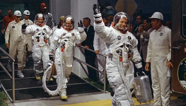 Apollo 11 crew wave while walking to shuttle