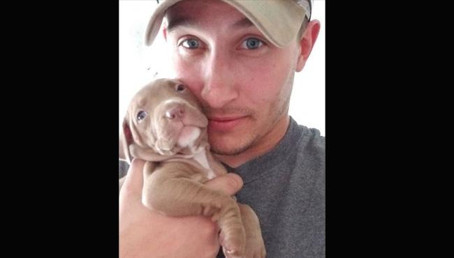 Man holding puppy in hand