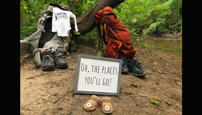 Little explorer baby onesie and booties on riverbank with hiking gear