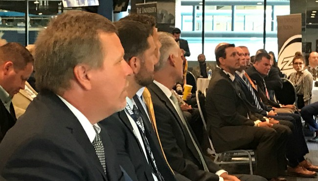 Seven coaches seated in one row at event