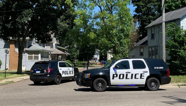 Two Kalamazoo police cruisers and police tape block a street