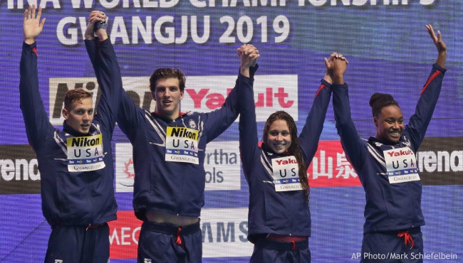The U.S. team from left, Caeleb Dressel, Zach Apple, Mallory Comerford, and Simone Manuel stand on the podium to receive their gold medal in the mixed 4x100m freestyle relay at the World Swimming Championships in Gwangju, South Korea, Saturday, July 27, 2019. (AP Photo/Mark Schiefelbein)
