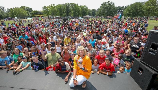 Maranda crouches on stage in front of thousands of standing people at Garfield park
