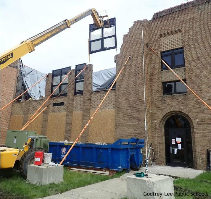 Construction equipment holds window above broken wall of school