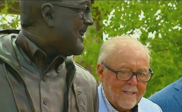 A photo of Peter Secchia standing next to a statue of him in Millennium Park. (July 23, 2019)