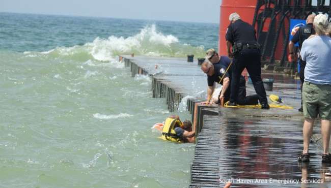 Rescuer and swimmer in water with rope extended from pier