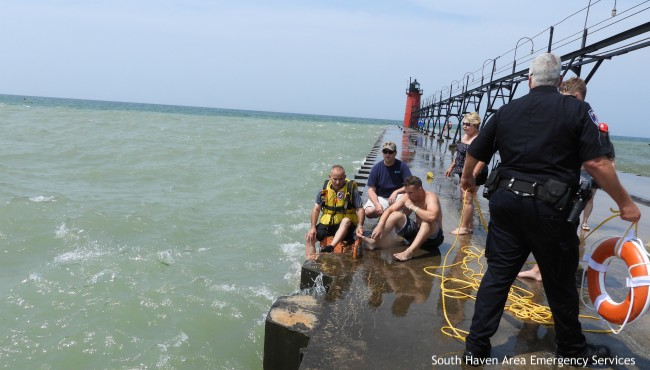 Swimmer rests on South Haven pier surrounded by rescuers