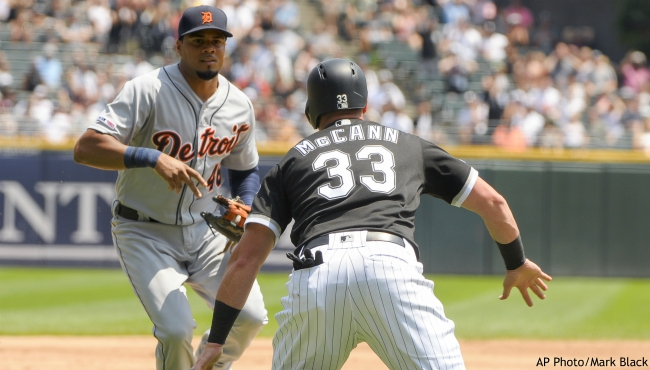 Chicago White Sox' James McCann (33) gets caught in a rundown between third and home before being tagged out by Detroit Tigers third baseman Jeimer Candelario (46), left, during the first inning of a baseball game Wednesday, July 3, 2019, in Chicago. (AP Photo/Mark Black)