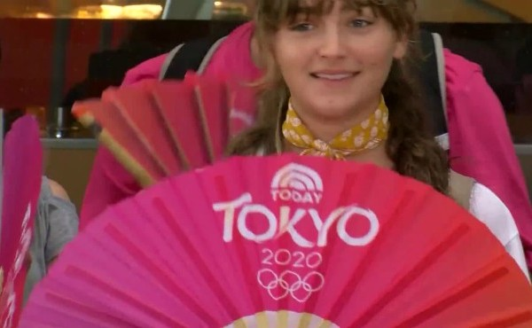 Woman holding fan with Tokyo Olympics printed on it