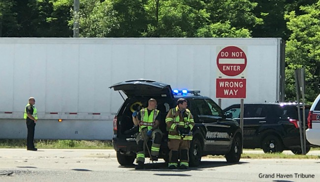 Firefighters sit in cruiser in front of semi-truck at crash scene