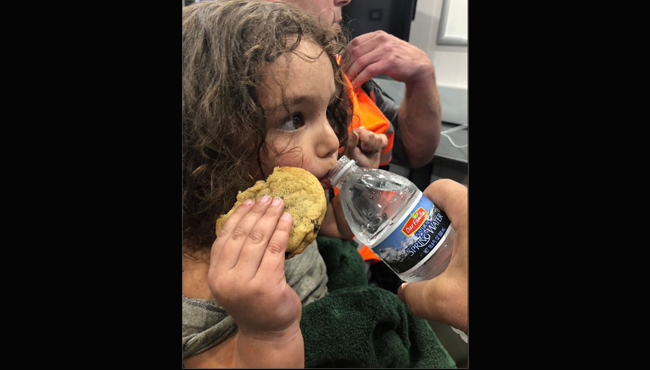 Gabriella takes a sip of water while holding a cookie