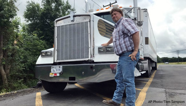 Truck driver Terry Button poses next to semi-truck