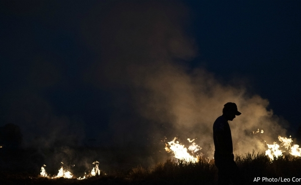 Neri dos Santos Silva, center, is silhouetted against an encroaching fire threat after he spent hours digging trenches to keep the flames from spreading to the farm he works on, in the Nova Santa Helena municipality, in the state of Mato Grosso, Brazil, Friday, Aug. 23, 2019. Under increasing international pressure to contain fires sweeping parts of the Amazon, Brazilian President Jair Bolsonaro on Friday authorized use of the military to battle the massive blazes. (AP Photo/Leo Correa)