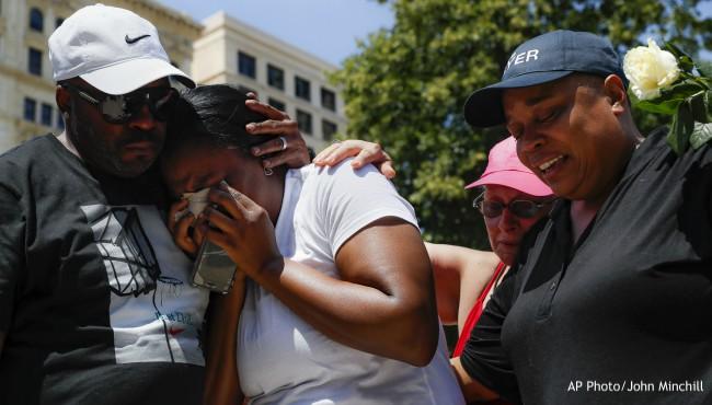 man hugs woman wiping away tears