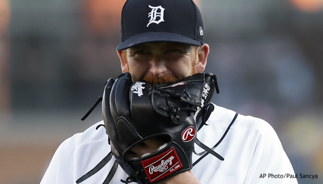 Baseball player bites his black leather glove