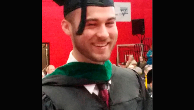 Man smiling in graduation cap and gown