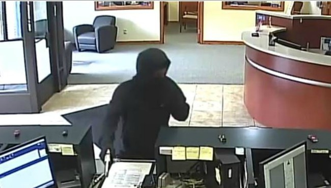 Suspect in black approaches bank desk