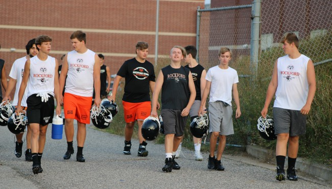 group of boys in athletic clothes walking down sidewalk