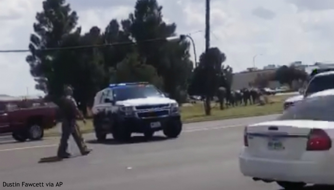 """In this image made from video provided by Dustin Fawcett, police officers guard on a street in Odessa, Texas, Saturday, Aug. 31, 2019. Police said there are """"multiple gunshot victims"""" in West Texas after reports of two suspects opening fire on Saturday in the area of Midland and Odessa. (Dustin Fawcett via AP)"""