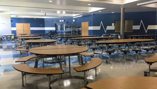 Blue and white painted walls with round tables in cafeteria
