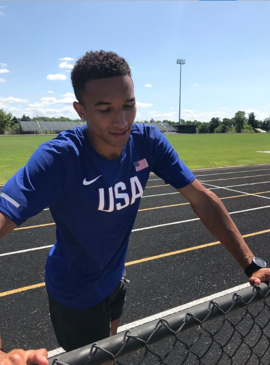 Donavan Brazier holds onto fence and stretches on track