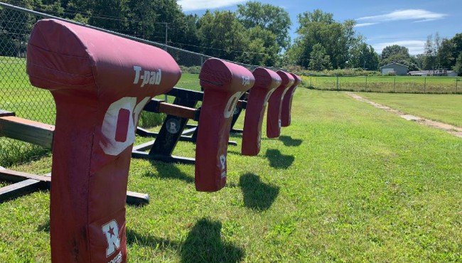 Football tackle practice equipment along fence on football practice field