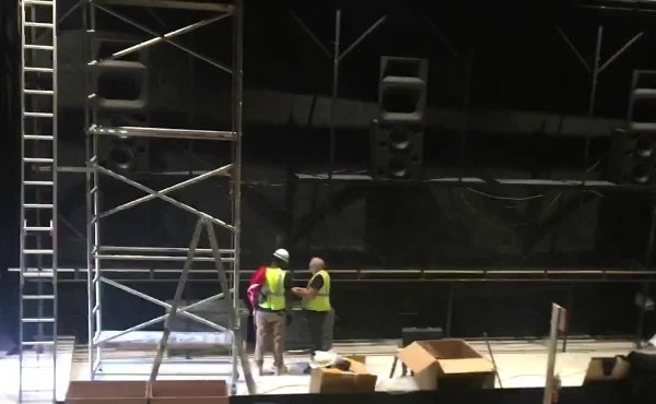 Construction crews on theater stage with boxes nearby