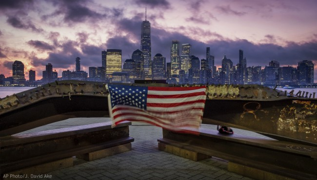 A U.S. flag hanging from a steel girder, damaged in the Sept. 11, 2001 attacks on the World Trade Center, blows in the breeze at a memorial in Jersey City, N.J., Sept. 11, 2019 as the sun rises behind One World Trade Center building and the re-developed area where the Twin Towers of World Trade Center once stood in New York City on the 18th anniversary of the attacks. (AP Photo/J. David Ake)