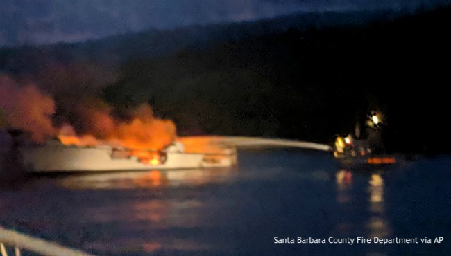 firefighters hose off burning boat