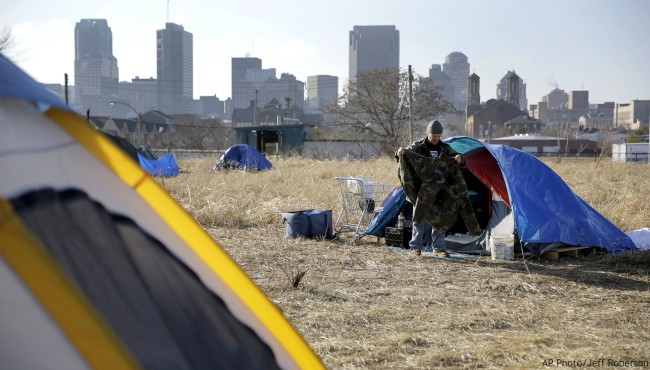 In this Tuesday, Jan. 27, 2015 file photo, Terry, cleans out his tent at a large homeless encampment, near downtown St. Louis. (AP Photo/Jeff Roberson)