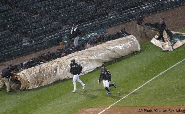 The Chicago White Sox grounds crew rolls out the field tarp as two players for the White Sox head into the dugout during a rain delay in the fourth inning of Game 1 of a baseball double-header against the Detroit Tigers, Friday, Sept. 27, 2019, in Chicago. (AP Photo/Charles Rex Arbogast)