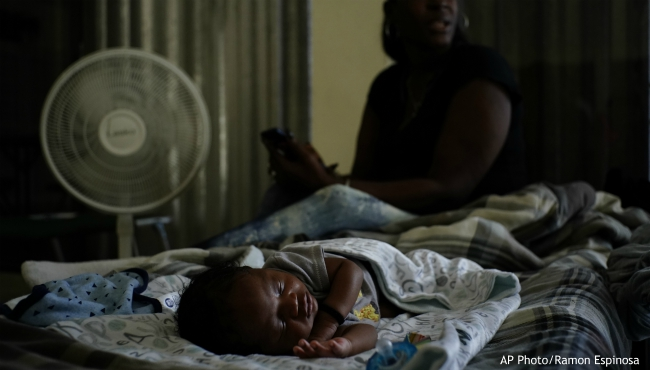 A baby sleeps inside a church that was opened up as a shelter for residents who will wait out Hurricane Dorian in Freeport on Grand Bahama, Bahamas, Sunday, Sept. 1, 2019. Hurricane Dorian intensified yet again Sunday as it closed in on the northern Bahamas, threatening to batter islands with Category 5-strength winds, pounding waves and torrential rain. (AP Photo/Ramon Espinosa)