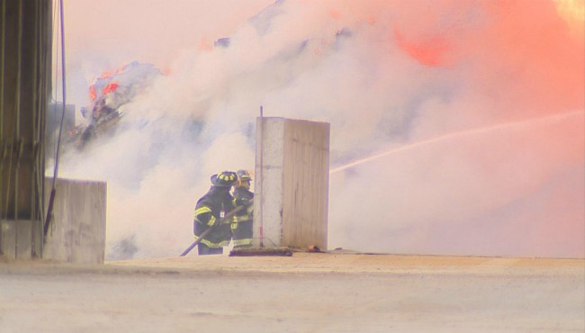 Firefighters spray flames