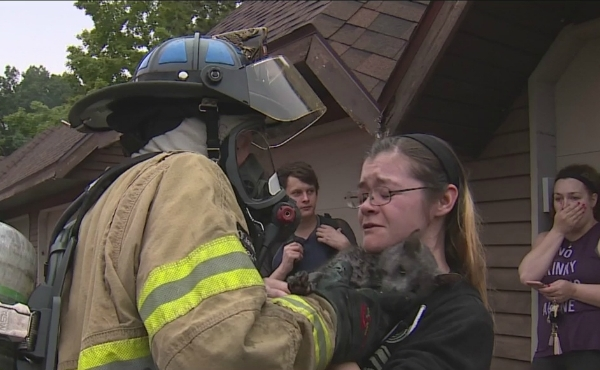 A photo of when a firefighter hands Sydney Varnagatas her cat, Winslow that was rescued from the fire. (Sept. 21, 2019)