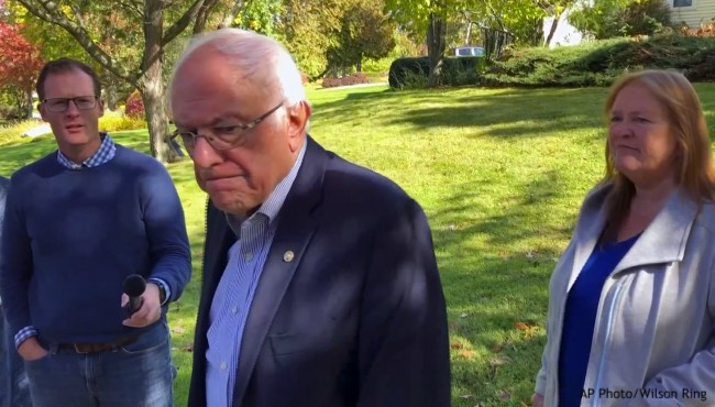 Bernie Sanders walking and talking with reporters