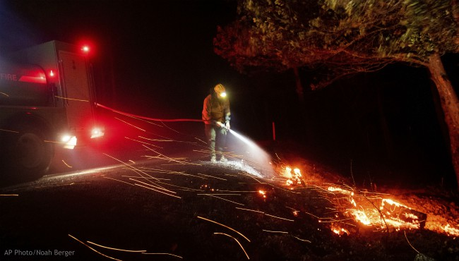 A firefighter battling the Kincade fire extinguishes a hot spot as strong winds send embers flying in Calistoga, Calif., on Tuesday, Oct. 29, 2019. (AP Photo/Noah Berger)