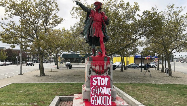 """A sign reading """"stop celebrating genocide"""" sits at the base of a statue of Christopher Columbus on Monday, Oct. 14, 2019, in Providence, R.I., after it was vandalized with red paint on the day named to honor him as one of the first Europeans to reach the New World. (AP Photo/Michelle R. Smith)"""