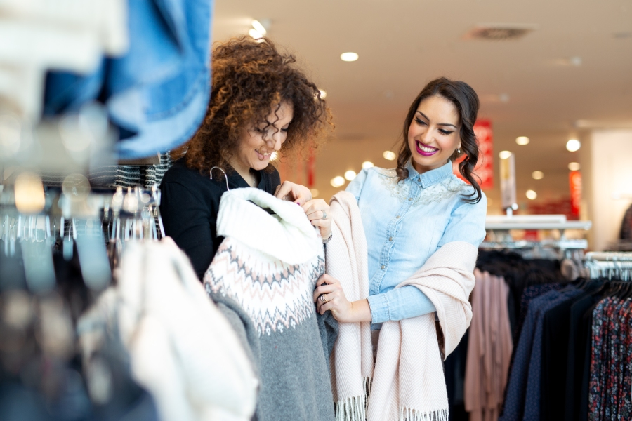 Two women looking at a sweater.