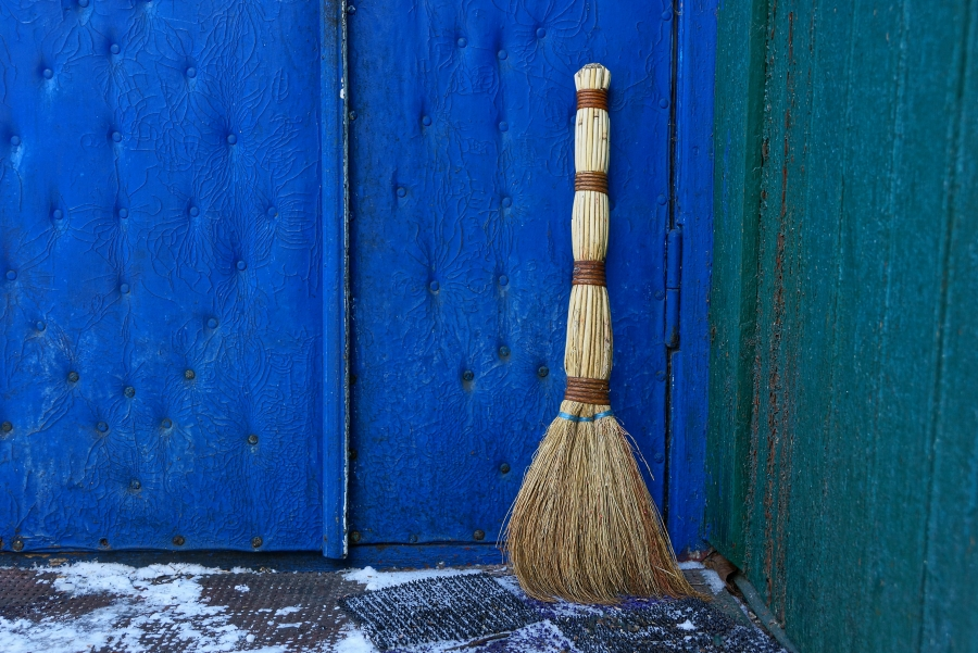 Broom against a blue barn.
