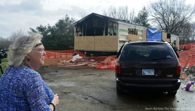 In this Sunday, April 7, 2019, file photo, Marie Chockley, a resident of the Timberline Trailer Court, north of Goodfield, Ill., surveys the damage that was caused by a Saturday night fire that killed five residents in a mobile home. (Kevin Barlow/The Pantagraph via AP, File)