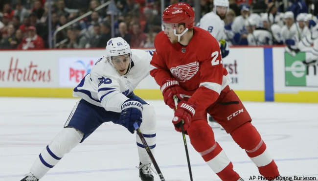 Toronto Maple Leafs right wing Ilya Mikheyev (65), of Russia, tries to steal the puck from Detroit Red Wings defenseman Dennis Cholowski (21), of the Czech Republic, during the first period of an NHL hockey game, Saturday, Oct. 12, 2019, in Detroit. (AP Photo/Duane Burleson)